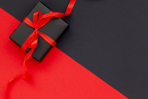 Black gift box with red ribbon on black and red background with copy space for text