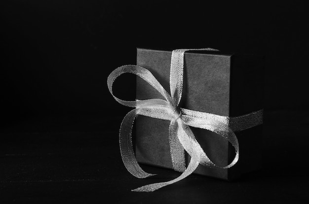 Black gift box with silver ribbon bow on black background