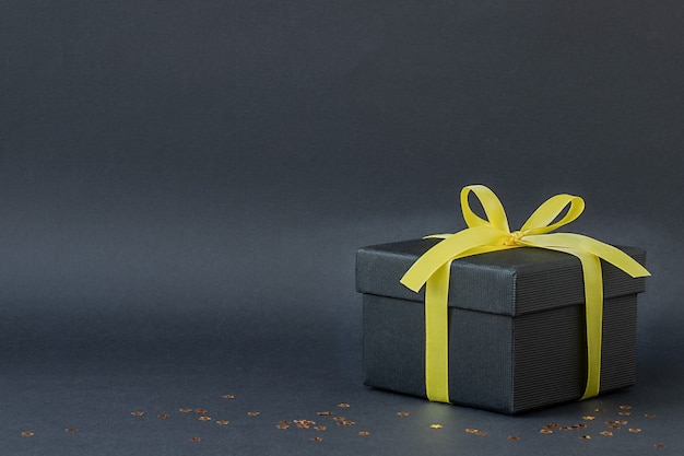 검은 바탕에 노란 리본이 달린 검은 선물 상자