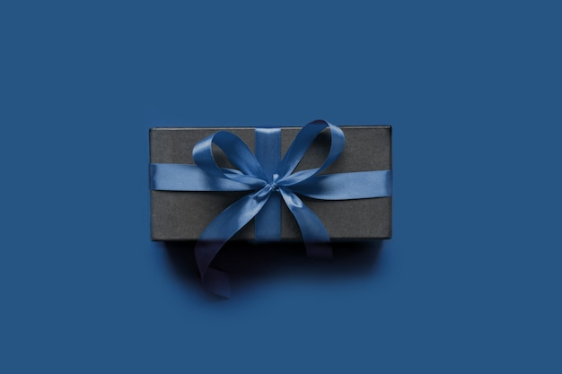 Black gift box wrapped with blue ribbon on classic blue surface.