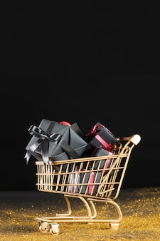 Black gifts in golden shopping cart