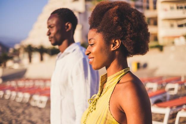 Черная девочка и мальчик молодые африканские люди стоя и улыбаются в летний день с бусинками солнца. красивый портрет молодых людей. традиционные редкие афро-волосы