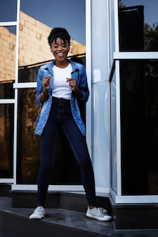 Black girl dances on a blue space outside the building