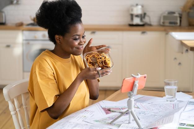 黒人の女の子の食品ブロガーの記録ビデオは、キッチンでパスタを食べるか、スマートフォンで友人や家族に電話します