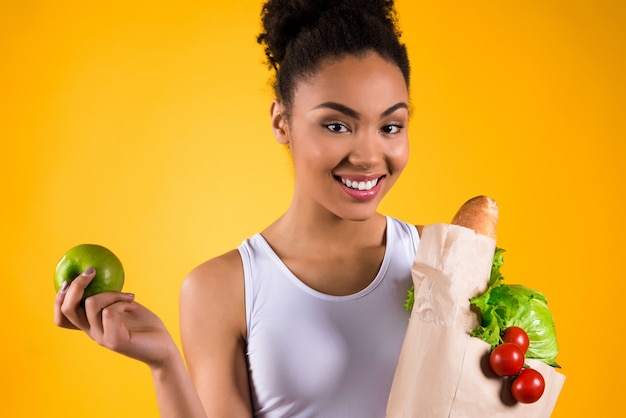 Black girl holding apple and groceries isolated.