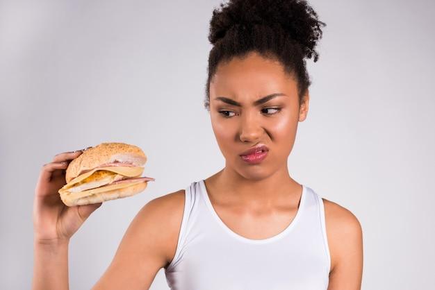 Black girl holding cheeseburger isolated.
