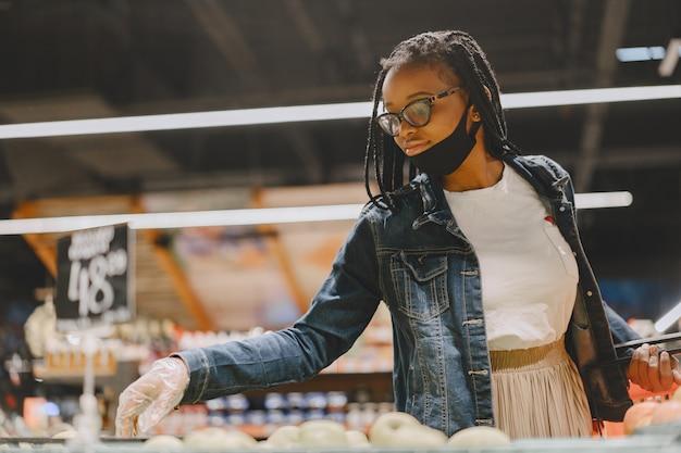 마스크에 흑인 여자는 음식을 구입