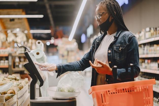 Черная девушка в маске покупает еду