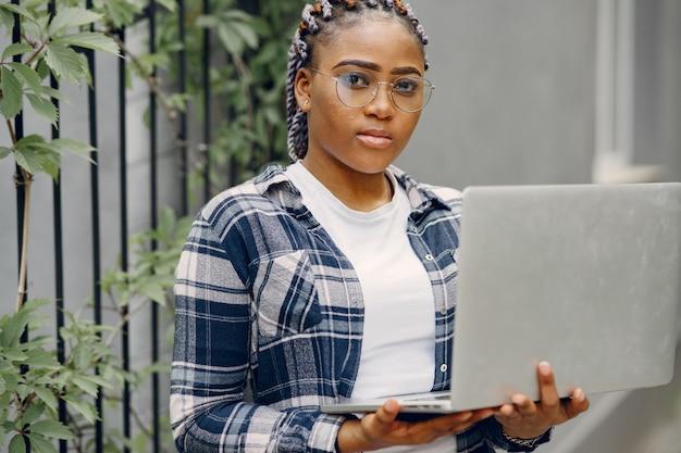 Черная девушка в летнем городе с ноутбуком