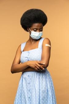 コビッド疑惑からのワクチン接種後の副作用を考えているフェイスマスクの黒人少女