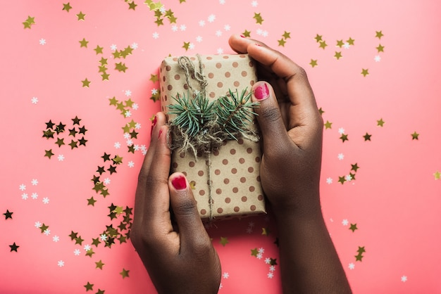 Black girl is holding a gift of kraft paper