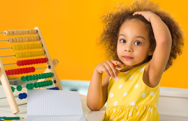 A black girl is puzzled by an example of arithmetic that she must count on the abacus