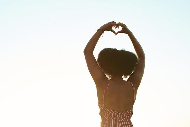 Черная девушка показывает сердце.