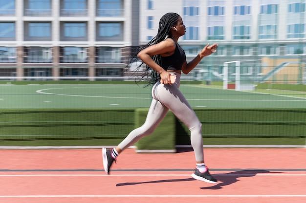 夏にスタジアムの外を走っている黒人の女の子は、携帯電話を着用し、ワイヤレスイヤホンのモーションブラーを保持します