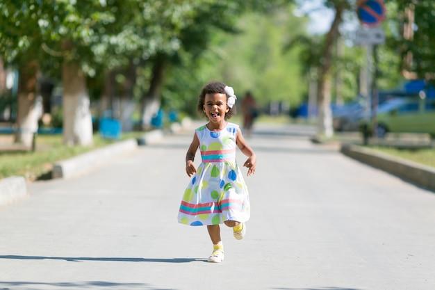 Black girl runs on the asphalt.