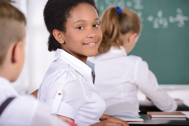 Black girl sitting at the table and smiling.