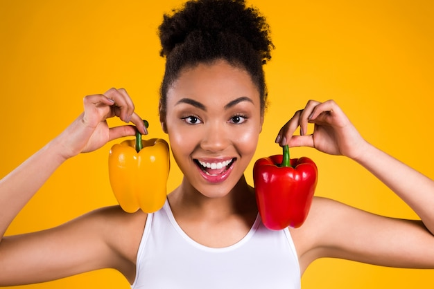 Black girl smiles and puts pepper on her shoulders.