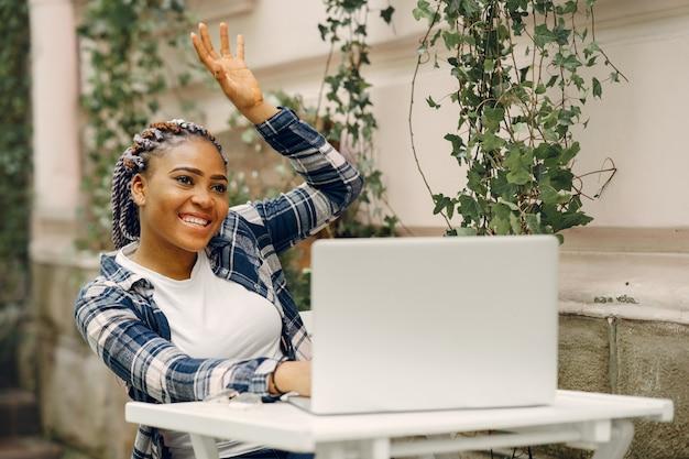 Ragazza nera in una città estiva con il laptop