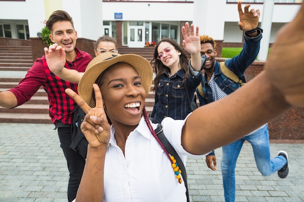 Black girl taking selfie with classmates