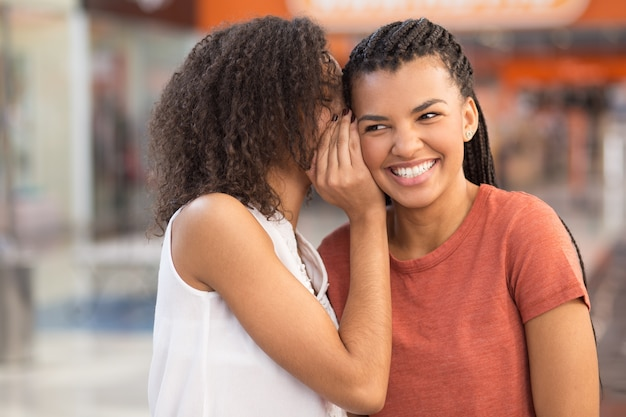 Black girl whispering secret to smiling girlfriend