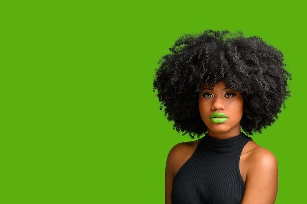 緑の背景の上に撮影された、カメラを見てアフロヘアスタイルの黒人の女の子。