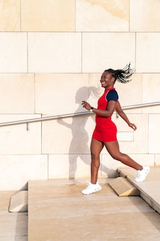 Black girl with afro hair walking up some steps smiling happily in the street of a city on a light beige wall in a colourful red dress