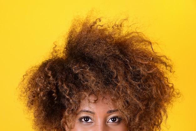 アフロヘアスタイルの黒人の女の子がフレームから覗きます。