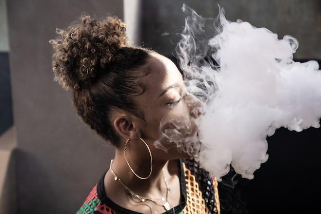 巻き毛と汽船で喫煙大きなイヤリングと黒の女の子