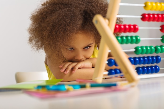 A black girl in a yellow dress is puzzled by an example of arithmetic girl portrait with abacus