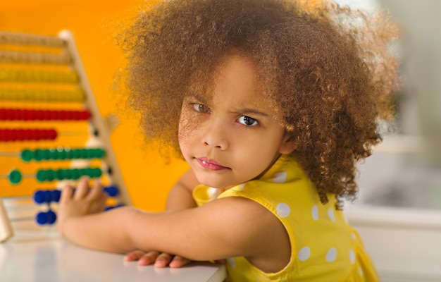 Black girl in a yellow dress is puzzled by an example of arithmetic portrait via a counting device