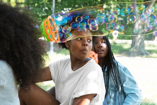 Черные девушки играют с мыльными пузырями