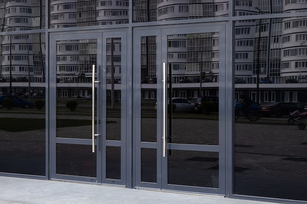 Black glass doors reflecting block of flats standing in the opposite side