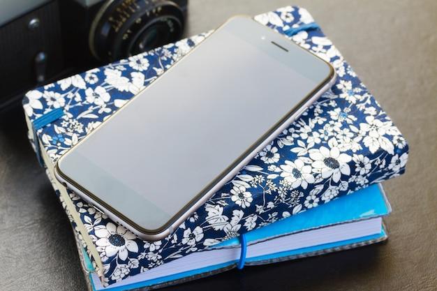 Черный стеклянный телефон с стопкой ноутбуков