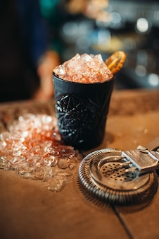 Black glass with ice, cold crystals on bar counter