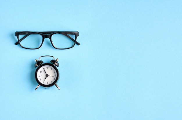 Black glasses and alarm clock on blue surface.