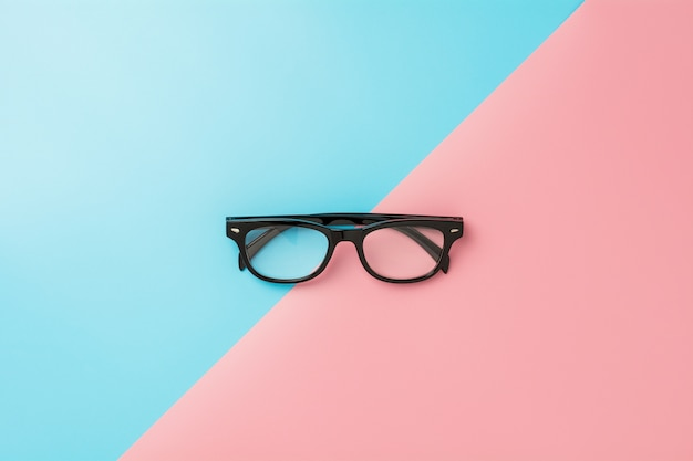 Black glasses on blue and pink background.