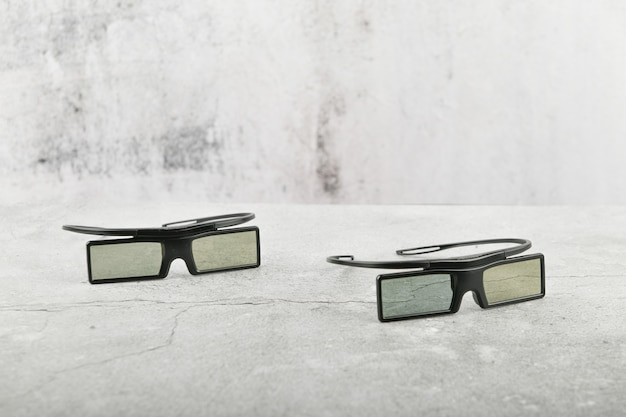 Black glasses on concrete background. two pairs of 3d glasses on a gray concrete surface. top view, copy space. two pairs of 3d glasses on a gray concrete surface. top view, copy space