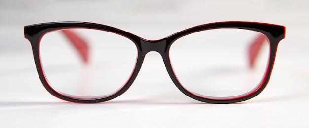 白い背景に赤い弓とビジョンのための黒いメガネ。クリッピングパス。