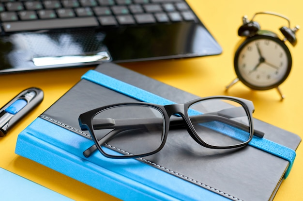 Black glasses, notebook, usb flash and laptop keyboard on blue and yellow surface.