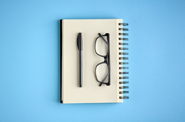 Black glasses, pen and paper notebook on blue surface.
