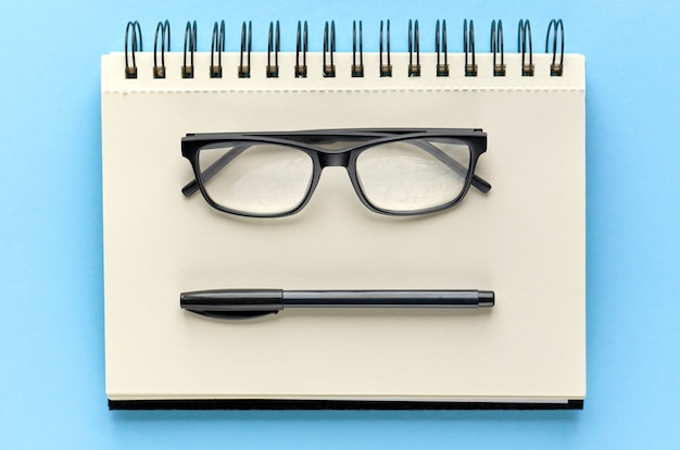 Black glasses, pen and paper notebook on blue surface  Photo