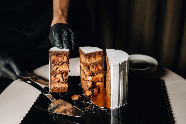 A black-gloved chef is slicing a chocolate wedding cake