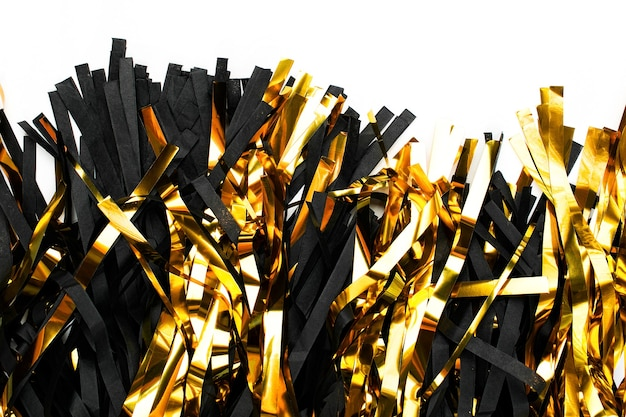 Black and gold fringe tassel garland on white background. flat lay, top view. holiday concept