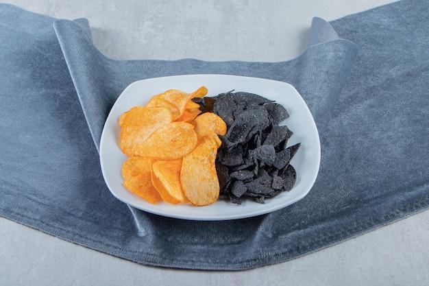 Chip croccanti neri e dorati sul piatto bianco con il panno.