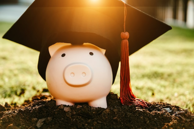 A black graduate hat, brown tassels and a pink piggy bank lay on the black ground.
