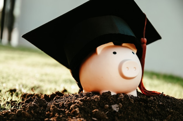 A black graduate hat, brown tassels and a pink piggy bank lay on the black ground. Premium Photo