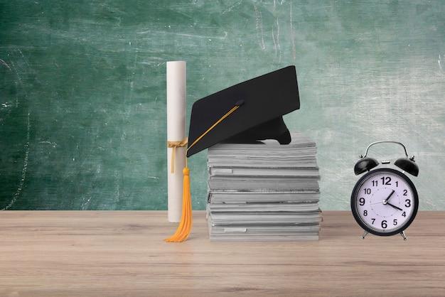 나무 배경에 검은 졸업 모자, 학위 증명서 및 알람 시계 속도