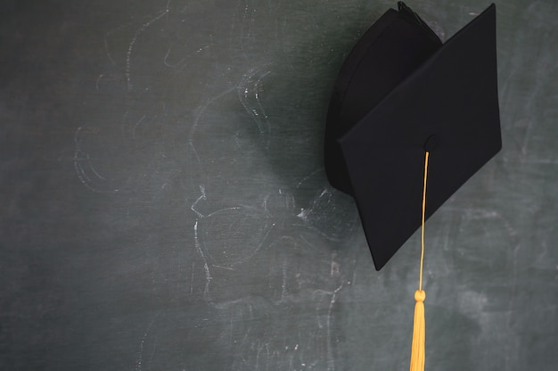 Black graduates hat hung on the blackboard