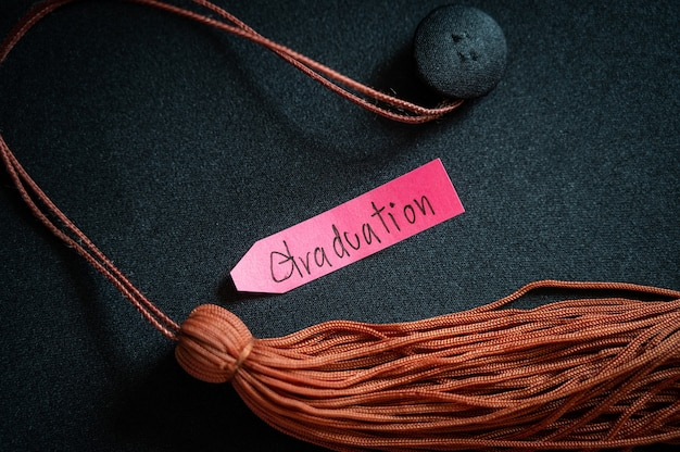 Black graduation cap and brown tassel place on wooden table