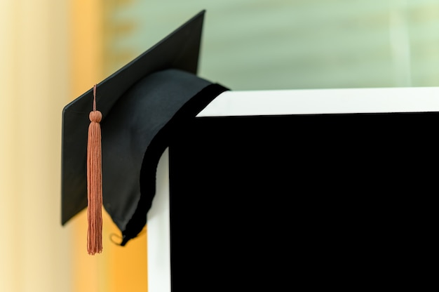 Black graduation cap placed on a computer monitor